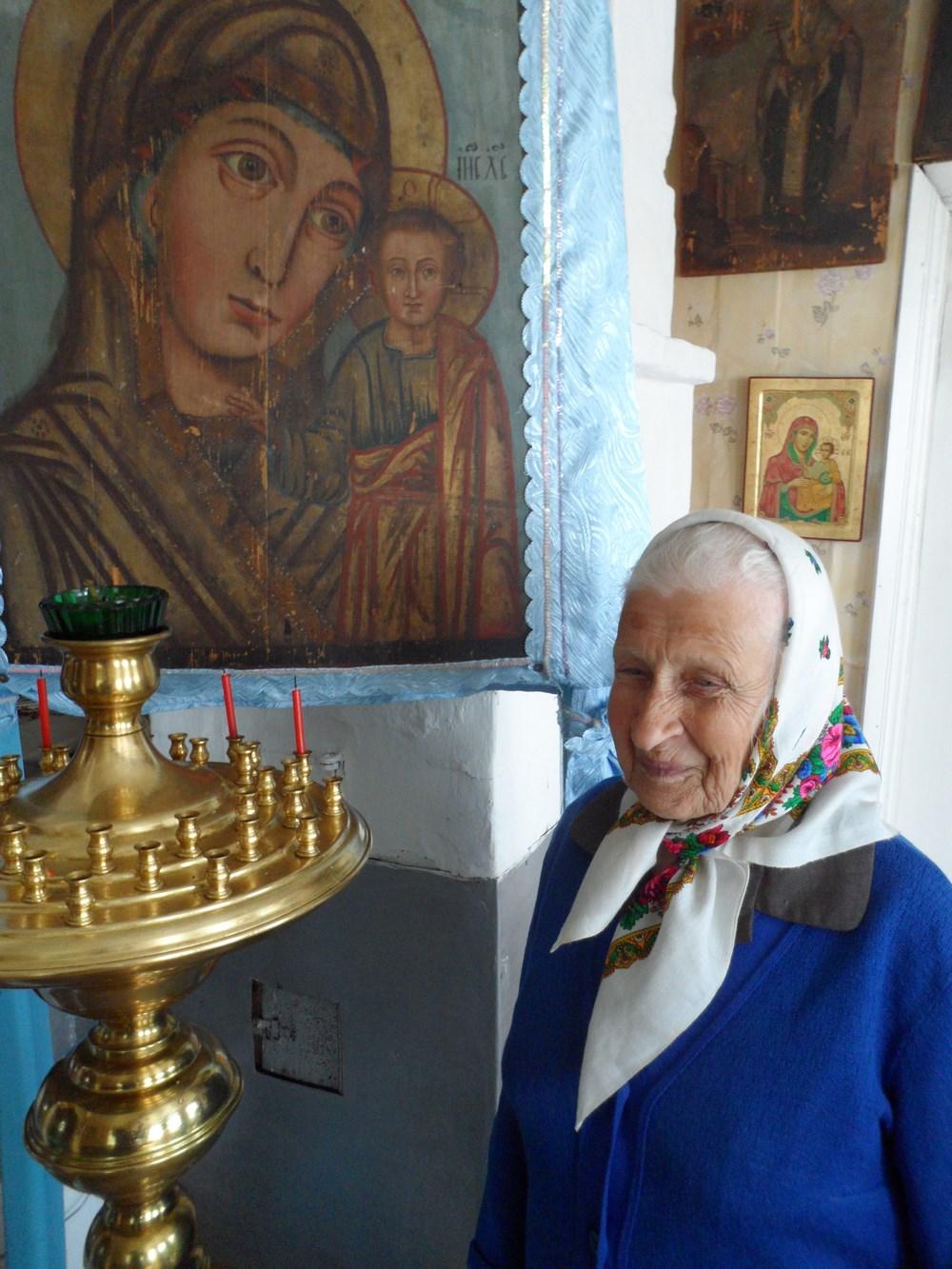 Вера Дмитриевна Голикова ухаживает за подсвечником около Казанской иконы